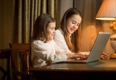 2 девушки сидя на таблице и используя компьтер-книжку Стоковая Фотография