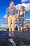 2 девушки сидя на луче Стоковое Фото