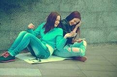 2 девушки сидя на улице Стоковое Изображение RF