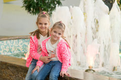 2 девушки сидя на фонтане в моле и joyfully взгляде к рамке Стоковое фото RF