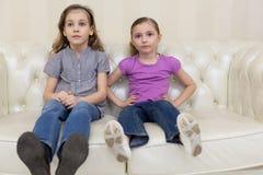 2 девушки сидя на sofaand смотря TV Стоковая Фотография