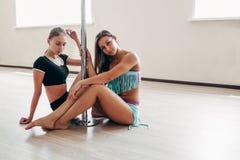 2 девушки сидя около поляка в студии тренировки Стоковые Изображения