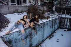 2 девушки сидя около пустого бассейна на зимний день Стоковое Изображение