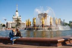 2 девушки сидя около фонтана приятельства людей Стоковая Фотография