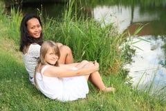 2 девушки сидя прудом Стоковые Изображения