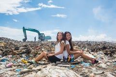 2 девушки сидя спина к спине на свалке мусора Стоковая Фотография RF