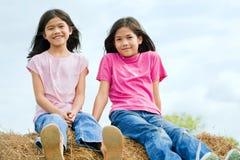 2 девушки сидя na górze haybale Стоковые Изображения