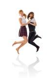 2 девушки скача и держа руки Стоковое фото RF