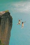 2 девушки скалы скача, против океана бирюзы Стоковые Изображения