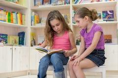 2 девушки сконцентрированы в библиотеке Стоковые Фотографии RF