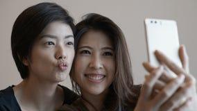2 девушки смешанных гонки азиатских принимая selfie с умным телефоном Стоковые Изображения RF