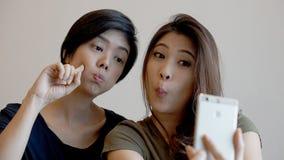 2 девушки смешанных гонки азиатских принимая selfie с умным телефоном Стоковое Изображение