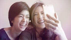 2 девушки смешанных гонки азиатских принимая selfie с умным телефоном Стоковые Фотографии RF