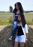 2 девушки смеясь над в поле Стоковое Фото