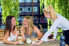 2 девушки смеясь над говорить к женскому кельнеру Стоковая Фотография