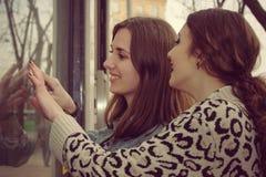 2 девушки смотрят в окно магазина Стоковые Фотографии RF