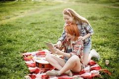 2 девушки смотря в таблетке на пикнике Стоковое фото RF