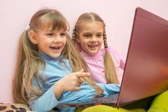 2 девушки смотря компьтер-книжку и смеясь над весело, одна указывают на экран Стоковая Фотография RF