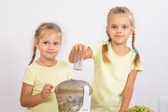 2 девушки смотря к рамке сжимая фруктовый сок в juicer Стоковые Фото