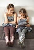 2 девушки смотря на экране таблетки Стоковая Фотография RF