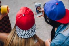 2 девушки смотря они фото на smartphone Стоковое Изображение RF