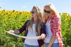 2 девушки смотря поле солнцецветов дорожной карты стоящее внешнее Стоковое фото RF