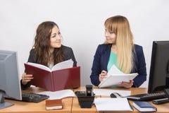 2 девушки соперников дела смотрят один другого пока сидящ на столе Стоковые Фотографии RF