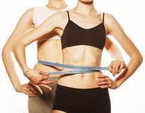 2 девушки спорта измеряя изолировали дальше Стоковая Фотография RF