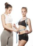 2 девушки спорта измеряя изолировали на белизне Стоковые Фотографии RF
