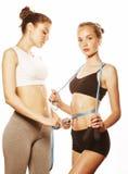 2 девушки спорта измеряя изолировали на белизне Стоковые Изображения