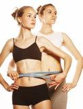 2 девушки спорта измеряя изолировали на белизне Стоковое фото RF