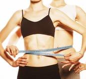2 девушки спорта измеряя изолировали на белизне Стоковые Фото