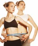2 девушки спорта измеряя на белизне Стоковые Фото