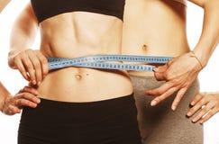 2 девушки спорта измеряя на белизне Стоковая Фотография RF