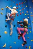 2 девушки спортсмена взбираясь на голубой стене Стоковое Фото