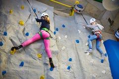 2 девушки спортсмена взбираясь на голубой стене Стоковые Изображения