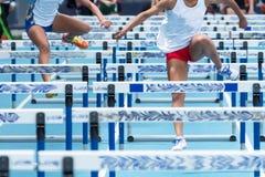 2 девушки средней школы участвуя в гонке барьеры на встрече следа Стоковое Изображение RF