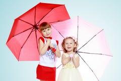 2 девушки стоят под зонтиками Стоковые Изображения