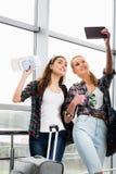 2 девушки стоят с чемоданами на авиапорте и смотреть таблетку Отключение с друзьями Стоковое Изображение RF