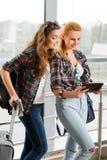2 девушки стоят с чемоданами на авиапорте и смотреть таблетку Отключение с друзьями Стоковые Фотографии RF