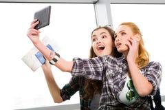 2 девушки стоят с чемоданами на авиапорте и смотреть таблетку Отключение с друзьями Стоковое Изображение