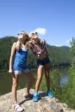 2 девушки стоя на утесе и наслаждаясь рекой Стоковое Изображение