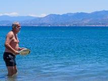 девушки стола голубого мальчика смотрят заниматься серфингом моря сидя Стоковые Изображения