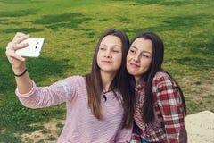 2 девушки сфотографированы мобильным телефоном Стоковое фото RF