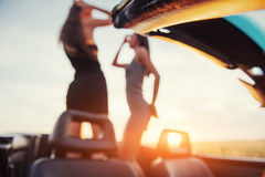2 девушки счастливой для того чтобы представить затем черный автомобиль Стоковые Фото