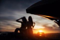 2 девушки счастливой для того чтобы представить затем черный автомобиль Стоковое фото RF