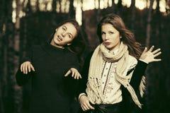 2 девушки счастливых моды предназначенных для подростков идя в осень паркуют Стоковая Фотография