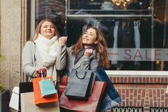 2 девушки счастливы с приобретением перед продажей текста Стоковое фото RF