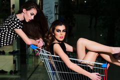 2 девушки с вагонеткой покупок Стоковые Изображения