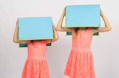 2 девушки с коробками на их головах Стоковая Фотография RF